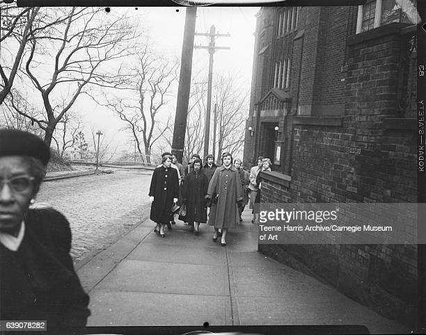 Nursing students from St John Hospital walking on sidewalk of Grace Memorial Presbyterian Church for funeral of fire victims Clarence Gary Hart...