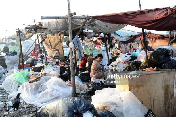 Nurtinah sorts the garbage Nurtinah a farm worker from Pucang Anom village Cerme subdistrict Bondowoso district East Java Province Indonesia was...