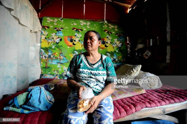 Nurtinah takes a break after working as a scavenger in her small hut Nurtinah a farm worker from Pucang Anom village Cerme subdistrict Bondowoso...