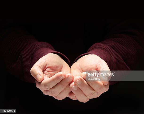 nurturing hands cupped, empty, clasped to hold something, black background - hands cupped stock pictures, royalty-free photos & images