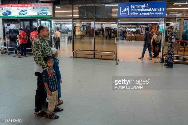 Nurul Islam along with his two kids wait to receive his wife Sumi Akter at Hazrat Shahjalal International Airport in Dhaka on November 15, 2019. -...