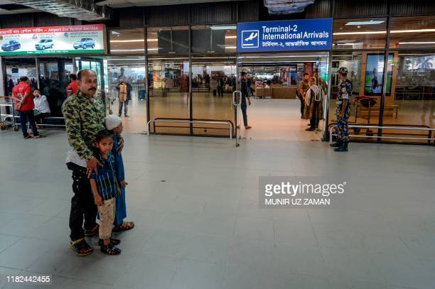 Nurul Islam along with his two kids wait to receive his wife Sumi Akter at Hazrat Shahjalal International Airport in Dhaka on November 15 2019...
