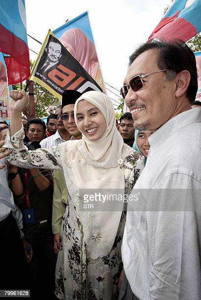 Nurul Izzah Anwar raises her first while accompanied by her father former deputy prime minister and defacto opposition People's Justice Party leader...