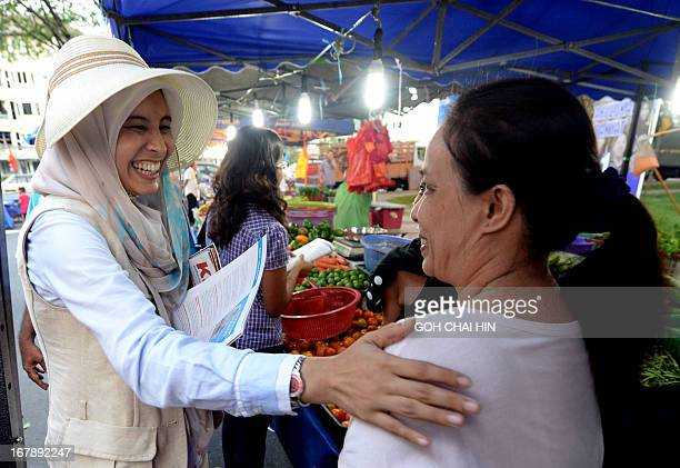 Nurul Izzah daughter of opposition leader Anwar Ibrahim and a Member of Parliament for Lembah Permai in Kuala Lumpur chats with a shopper as she goes...