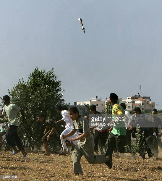 Palestinians runs for cover as a missile fired by the Israeli military is seen nearly hitting its target during an Israeli air strike on Hamas'...