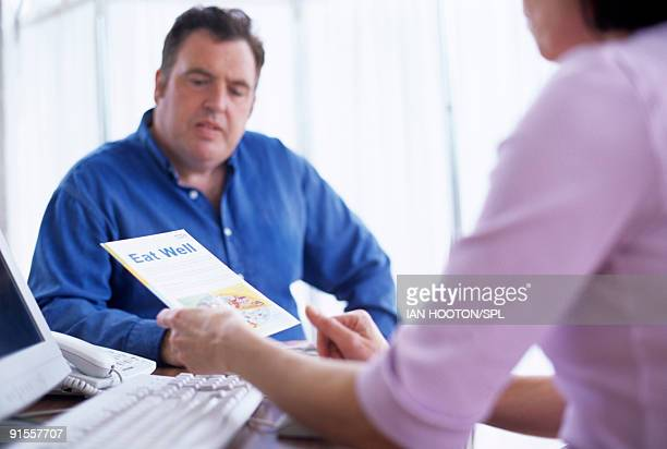 Nutritionist advising obese man on how to eat more balanced diet