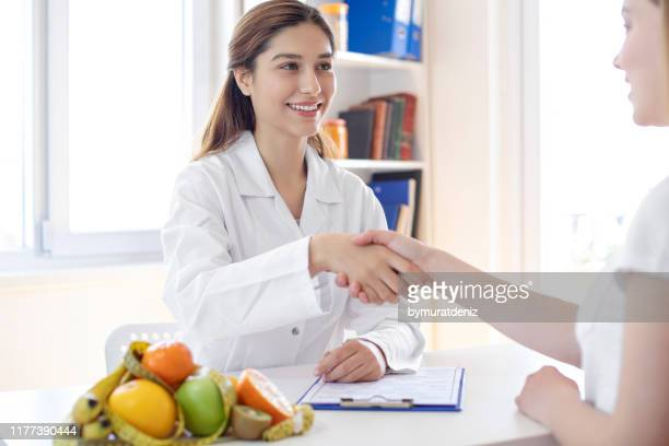 nutritionist hand shaking - nutritionist stock pictures, royalty-free photos & images