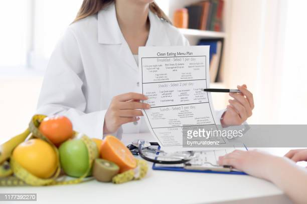 nutritionist showing nutrition plan - nutritionist stock pictures, royalty-free photos & images