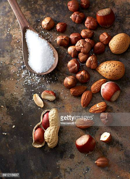 Nuts, almonds and wooden spoon of sugar