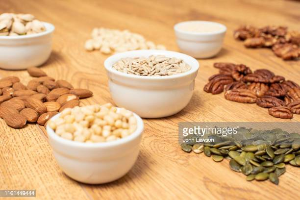 nuts and seeds on a table - magnesium stock pictures, royalty-free photos & images