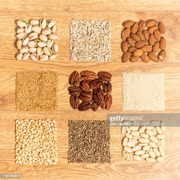 nuts and seeds on a wooden background - sesame stock pictures, royalty-free photos & images