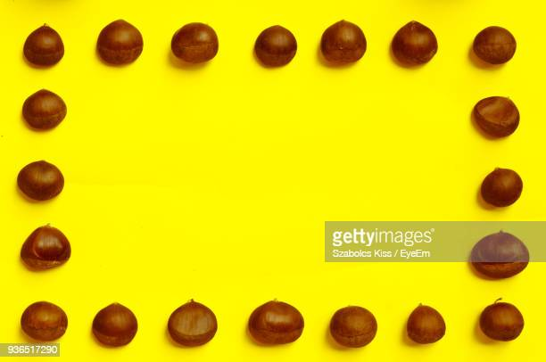nuts arranged on yellow background - chestnut food stock pictures, royalty-free photos & images