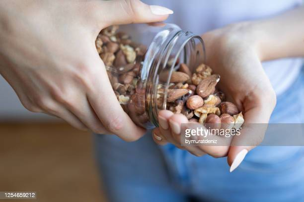 nuts in woman hands - almond stock pictures, royalty-free photos & images
