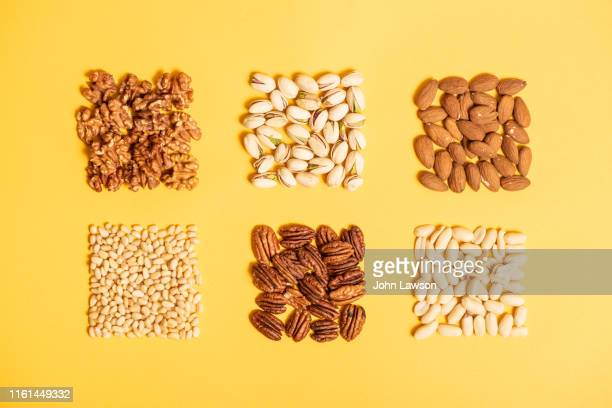 nuts on a yellow background - nut food stock pictures, royalty-free photos & images