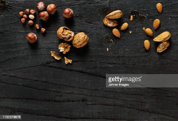 nuts on black background - アーモンド ストックフォトと画像