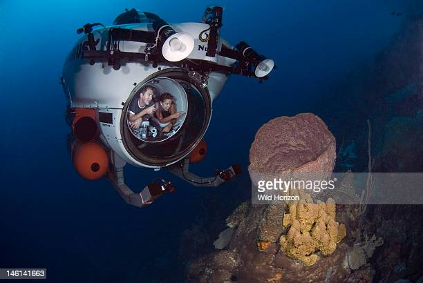 Nuytco mini submarine on coral reef with people looking at giant barrel sponge Depth was Seaquarium Curacao Netherlands Antilles Digital Photo
