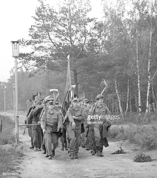 NVASoldaten einer in der Umgebung von Cottbus stationierten Militäreinheit marschieren mit Schaufeln und FDJFahne zu einem freiwilligen...