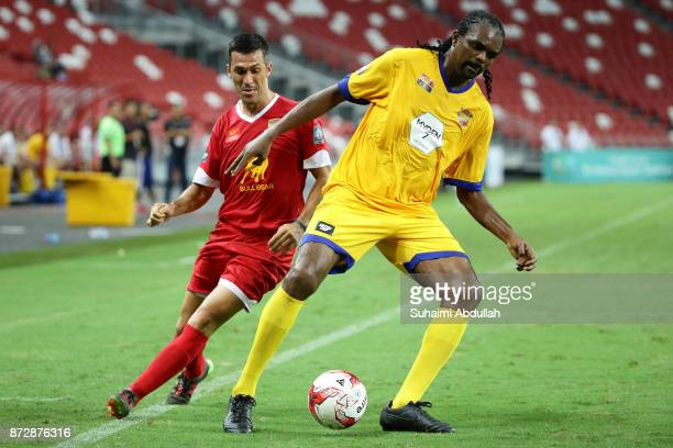 Nwankwo Kanu of Arsenal Masters shields the ball from Luis Garcia of Liverpool Masters during the Battle of the Masters at National Stadium on...