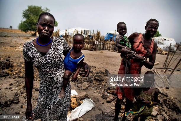 Nyakuma Tap and her older sister Nyakuoth Kuol hold their babies on the remnants of their former shelter in Dablual South Sudan on March 23 2017 They...