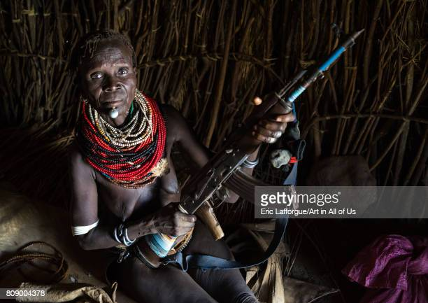 Nyangatom tribe woman holding a kalashnikov in her hut Omo valley Kangate Ethiopia on June 10 2017 in Kangate Ethiopia
