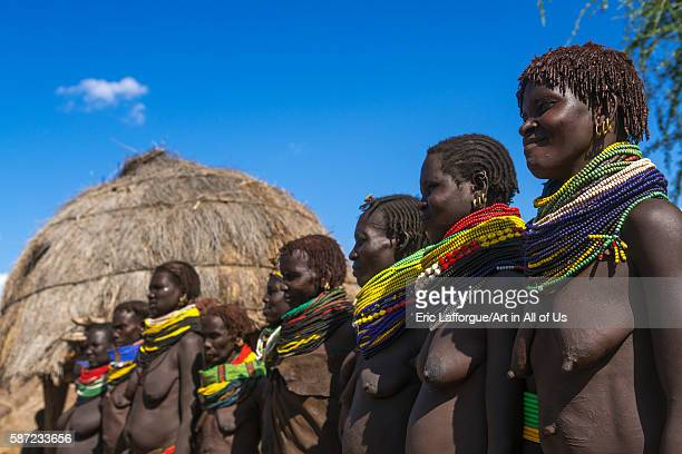 Nyangatom tribe women with huge necklaces in a line omo valley kangate Ethiopia on March 15 2016 in Kangate Ethiopia