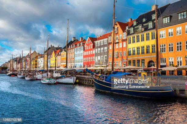nyhavn area of popular bar and restaurant at beautiful blue sky, with colorful facades of old houses and old ships in the old town of copenhagen, capital of denmark. - nyhavn stock pictures, royalty-free photos & images