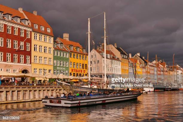 nyhavn (the new harbour) canal district. brightly coloured 17th century townhouses, bars, cafes, restaurants and historical wooden ships in copenhagen, denmark. - victor ovies fotografías e imágenes de stock
