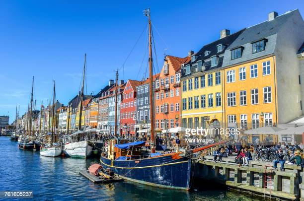 Nyhavn, the 17th century waterfront with row of colourful historic buildings, promenade and moored sailing ships in Copenhagen, Denmark.