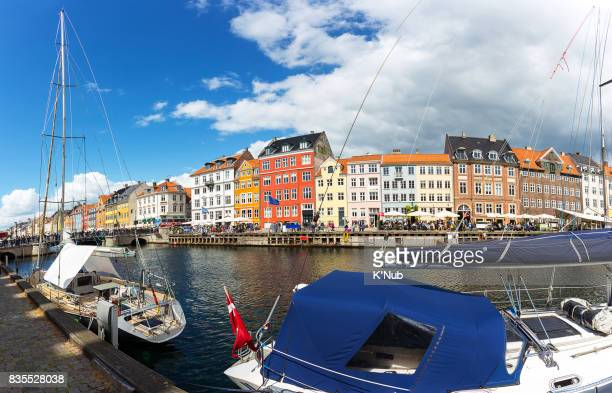 Nyhavn with colorful building along the canal and modern boat in