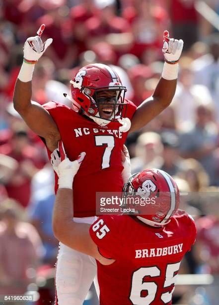 Nyheim Hines and teammate Garrett Bradbury of the North Carolina State Wolfpack celebrate after Hines scores a touchdown against the South Carolina...