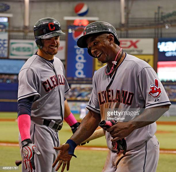 Nyjer Morgan of the Cleveland Indians is congratulated by Lonnie Chisenhall after scoring during the sixth inning of a game against the Tampa Bay...