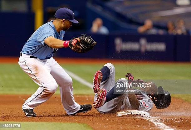 Nyjer Morgan of the Cleveland Indians slides into first past James Loney of the Tampa Bay Rays and is eventually called safe on an overturned replay...