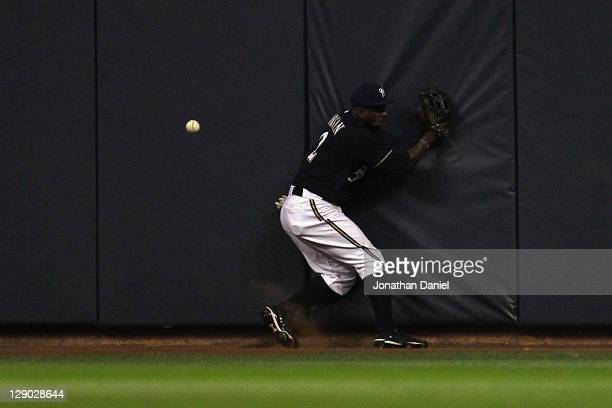 Nyjer Morgan of the Milwaukee Brewers runs into the wall after he couldn't make a play on a double hit by Albert Pujols of the St Louis Cardinals in...