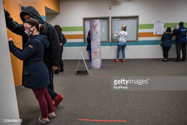 Nyjianah Zeigler, 20 helping Cristian Sepuol to fill out a voter registration form in Manchester, NH. Both were voting in a presidential election for...