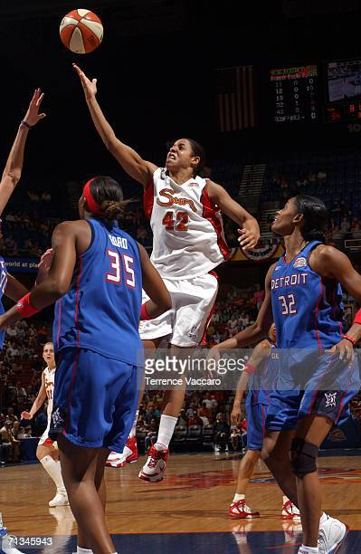 Nykesha Sales of the Connecticut Sun goes to the basket against Cheryl Ford and Swin Cash of the Detroit Shock at Mohegan Sun Arena in Uncasville...