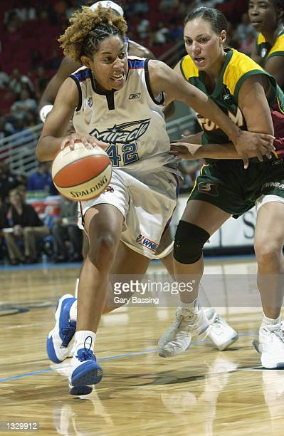 Nykesha Sales of the Orlando Miracle drives to the basket past Adia Barnes of the Seattle Storm in the game on July 25 2002 at TD Waterhouse Centre...