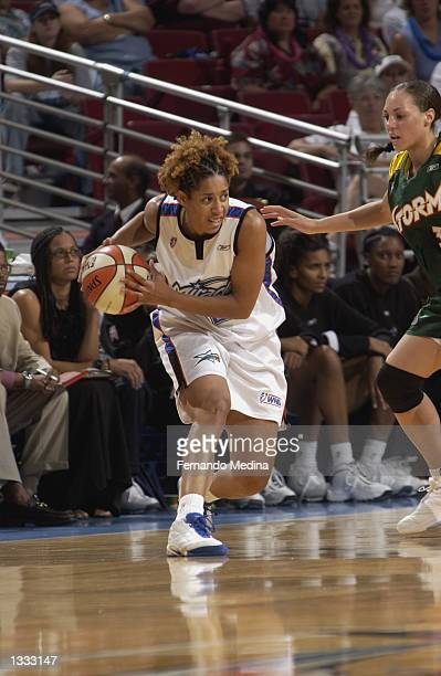 Nykesha Sales of the Orlando Miracle is defended by Adia Barnes of the Seattle Storm in the game on July 25 2002 at TD Waterhouse Centre in Orlando...