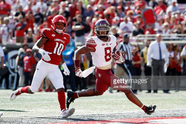 Nyqwan Murray of the Florida State Seminoles runs into the end zone for a 17yard touchdown after catching a pass ahead of Rodjay Burns of the...
