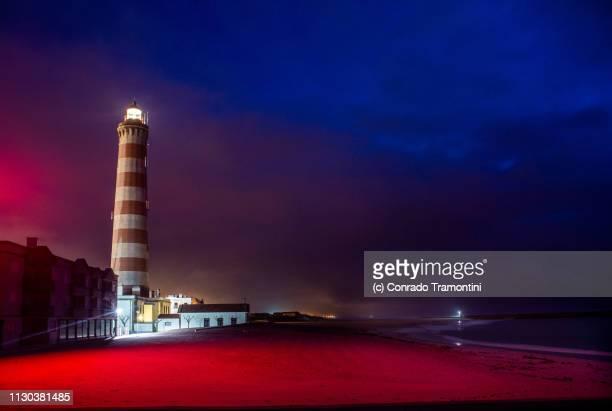 o farol de aveiro brilha sobre a praia de portugal iluminada pela luz vermelhoa do luminoso