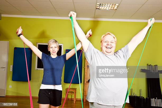 o verweight man and slim woman exercising with bands - skinny man fat woman stock pictures, royalty-free photos & images