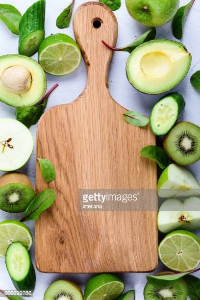 Oak wood cutting board  with fresh organic green fruits and vegetables