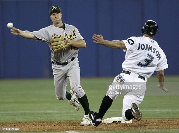 Oakland A's 2B Mark Ellis throws to first base to complete a double play over sliding Toronto Blue Jay Reed Johnson in MLB action at Rogers Centre in...