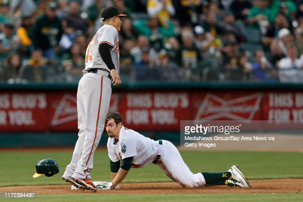 Oakland Athletics' Billy Burns is safe at third on a base hit by Oakland Athletics' Coco Crisp against Baltimore Orioles' iManny Machado n the first...