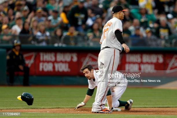 Oakland Athletics' Billy Burns is safe at third on a base hit by Oakland Athletics' Coco Crisp against Baltimore Orioles' Manny Machado in the first...
