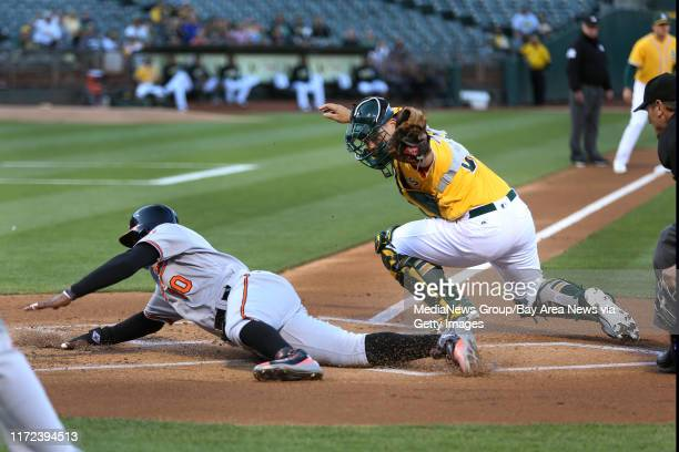 Oakland Athletics catcher Bruce Maxwell tags out Baltimore Orioles' Adam Jones at home in the first inning of a MLB game at O.co Coliseum in Oakland,...