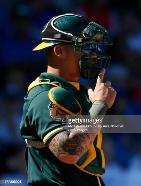 Oakland Athletics catcher Bruce Maxwell's right arm tattoo is visible as he warms up the pitcher Saturday Feb 25 during a Spring Training game in...