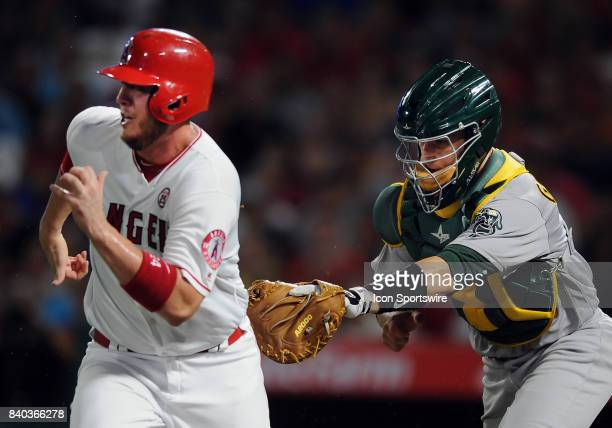 Oakland Athletics catcher Dustin Garneau chases and tags Los Angeles Angels of Anaheim first baseman CJ Cron out during a run down back towards third...