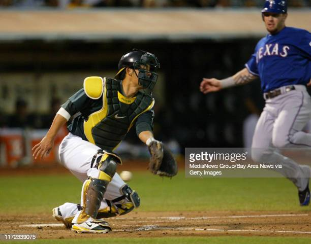 Oakland Athletics' catcher Kurt Suzuki left fails to catch the throw as Texas Rangers' Josh Hamilton is about to score on Michael Young's single in...