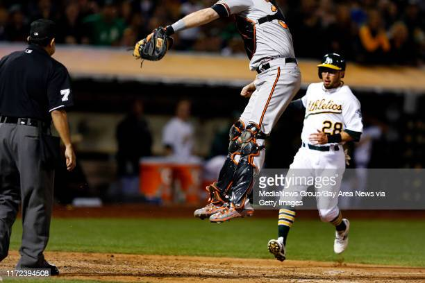 Oakland Athletics' Eric Sogard scores on a double by Billy Burns as Baltimore Orioles catcher Matt Wieters leaps for the throw at home in the fifth...