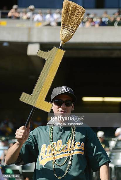 Oakland Athletics fan Jordan Perez holds up a broom with the number one hoping that the Athletics will defeat the Texas Rangers sweeping the series...